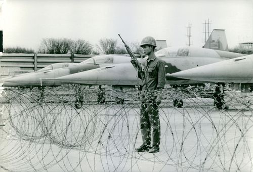 A soldier standing, holding a riffle, with fighter planes behind him, in Vietnam. November 16, 1972