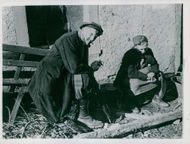 An elderly German civilian and his wife resting on the side of the road, in Germany.