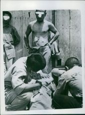 A Japanese Army doctor who was captured by U.S. forces fighting on Okinawa, treats some of his wounded countrymen during Japan War.