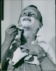 Emilio Schuberth photographed shaving his face.