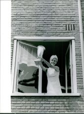 Miss Europe 1964 winner, Elly Koot holding and showing her trophy in the window