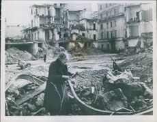 An old woman hunts for firewood in the rubble heaps in Anzio one year after Allied forces made landings, January 22, 1944.