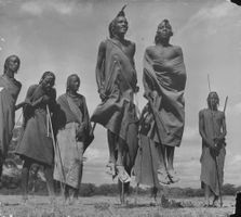 "Two of the ""moran"" (Masai warriors) do a stiff-legged dance, a circumcision ceremony."