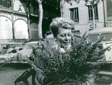 Gabrielle Marcilhacy, wife of Pierre Marcilhacy holding a plant, 1965.