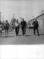 A woman walking with a man on sea port.