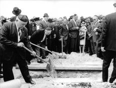 People gathered around a grave, putting soil over freshly digged grave.