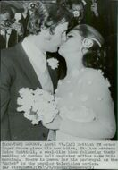Roger Moore gives her new bride, Luisa Mattioli, a kiss after their wedding at the Caxton Hall Register Office