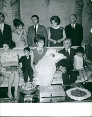 Farah Pahlavi and Mohammad Reza Pahlavi holding a newborn baby and sitting on couch with other people while few people standing behind.