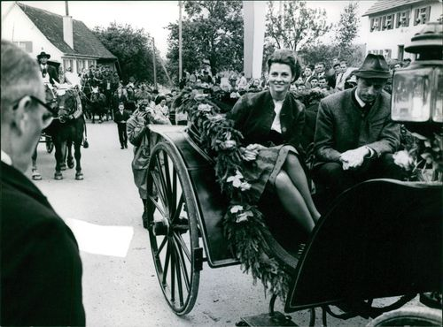 Man and woman riding on a cart, people looking at them.