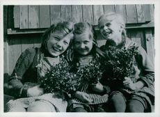 Three German girls, Vera, Irene and Ursula, are pictured March 13, 1945, at a camp in captured Bedersdorf; they looking towards the camera with smiling face