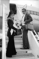Roger Vadim with his wife standing on staircase.