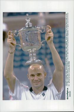American tennis player Andre Agassi holds up the cup after the win in the final against Todd Martin in the US Open 1999