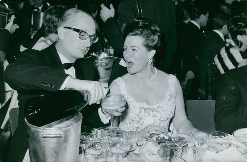 Bettina with a man in a party and having drink.