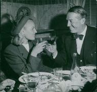 Maurice Chevalier having a drink in a restaurant.