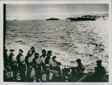The first picture of french troops France, showing soldiers wearing lifebelts aboard french ship in the background escorting warships can be seen silhouetted against the sun, 1940