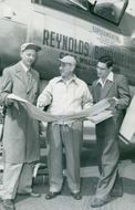 Around the airman Milton Reynolds studying the map with its pilot Captain William Odlum