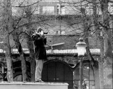 The East German embassy official photographs protesters from the royal garden's great scene.