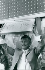 Kirk Douglas showing his hand imprint on clay.