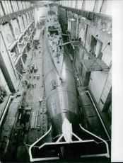 A view of inside a facility where people are working on a torpedo during the involvement of France in war 1967.