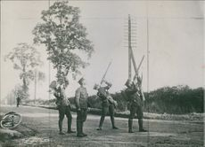 Soldiers standing and firing towards the sky.