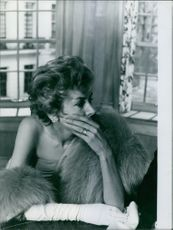 Kay Kendall covering her mouth with her hand.