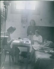 Women in prison cell, illuminating with dim light.