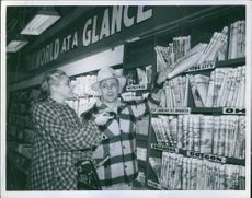 Newspaper vendor helping Patricia Wheel to get  a newspaper at the store from her hometown.
