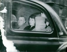Miss Remington inside a car and sat between two men, 1960.