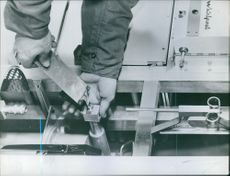 A photo of a man holding tool and opening the screws of a machine. 1961.
