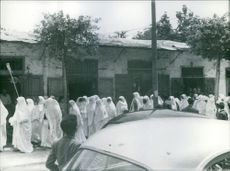Group of women in white dress are walking together on the road.