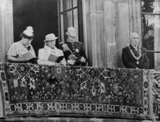 Queen Juliane reading standing on the balcony giving the public appearance to the people.