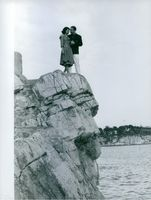 Prince Sadruddin Aga Khan standing on a cliff with his wife Nina Dyer.