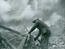 A photo of a Rescue crew in Sweden sawing the wood that obstructs the way after a fire hit in Rosersberg
