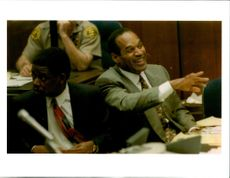 In a lighter moment during his double-murder trial, defendant O.J Simpson laughs and points during sidebar conference.