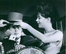 Horst Buchholz with a young lady placing a hat properly on his head, 1962.