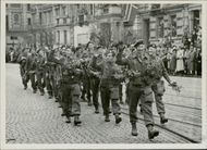 Soldiers marching the streets of Oslo with flowers and civilians.