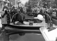 Prinsessan Anne in a car which is piercing through the sea of Photographers.