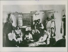 """A group of people being photographed inside a room.  """"England?"""""""
