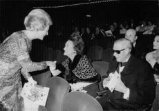The Duke of Windsor with his wife Wallis Simpson (the Duchess of Windsor) meeting another lady while inside a theater.