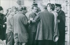 Men arguing with each other, while policemen trying to calm them down.