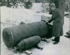 A man standing beside of a blaster bomb during Sweden war II.