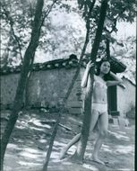A photo of woman standing in the bikini posing and holding tree.