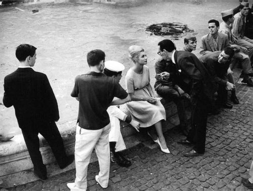 Surrounded by other men, an old man can be seen talking to the beautiful lady. 1960