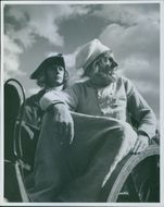 Two men riding on horse cart and looking at something during a scene in a 1944 film, Kungajakt.