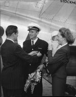 Captain Torsten Boltenstern has passed his millionth kilometers and receives  flight millionaire needle on his uniform while wife Eva, and son Michael looks.