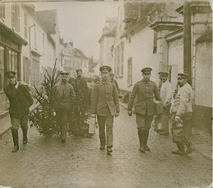 Soldiers walking and carrying trees. 1916.