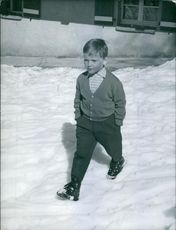A boy walking outside on the snow.