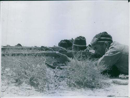 The Royal Corps of Colonial Troops hiding in the grass, 1940.