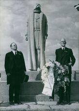 Two men standing beneath a statue and looking towards the camera.