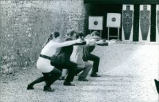 Three men and a woman firing a gun. 1971